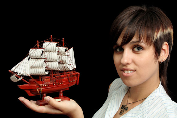 smiling girl holding a model sailing ship