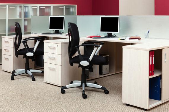 office interior with ergonomic seating, desks, and desktop computers