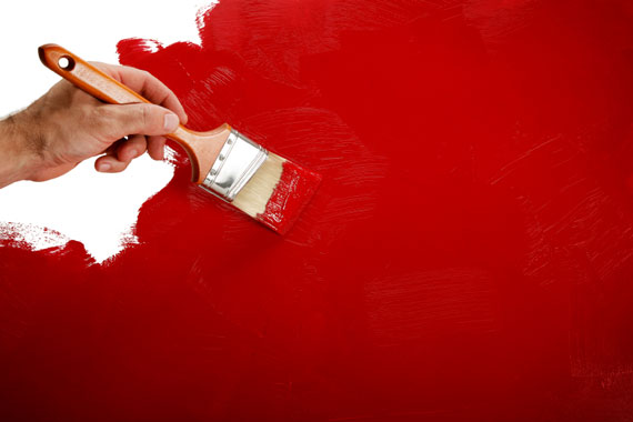 painting a house wall with a paintbrush