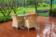 wicker furniture on a ground-level wooden deck